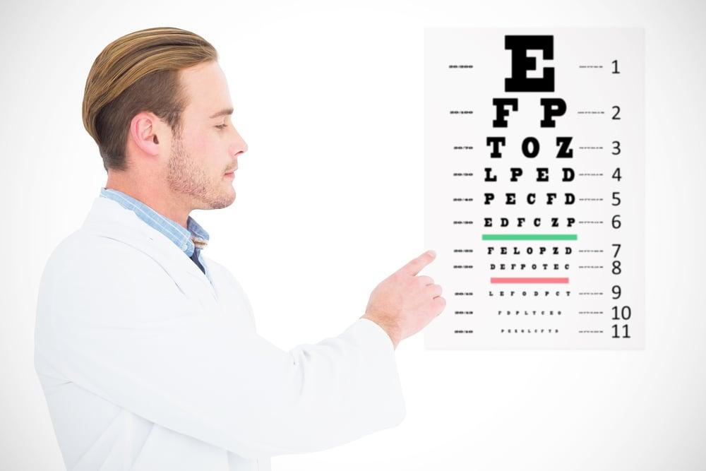 Optician in coat pointing eye test against eye test